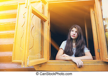 pretty teen girl in country wooden window