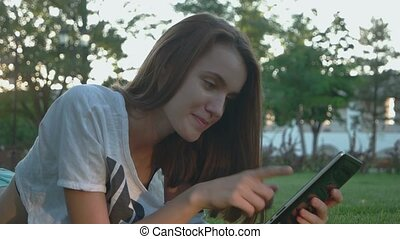 Pretty teen girl is working in internet outdoors
