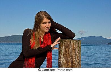 Pretty Teen Girl Leaning on Ocean Pole