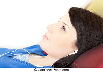 Pretty teen girl listening music lying on a sofa