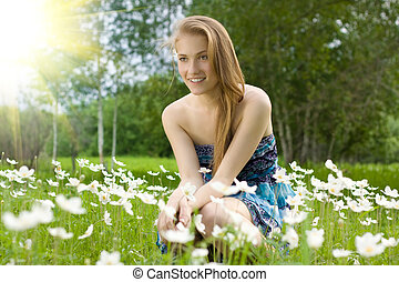 pretty teen girl on the field with snowdrops