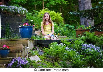pretty teen girl sitting in a garden