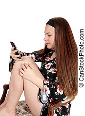 Pretty teen girl sitting on a chair looking at her cellphone