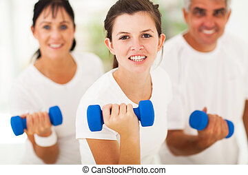 teen girl working out using dumbbell with parents