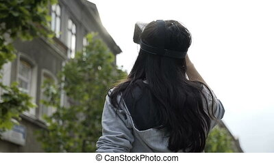 Pretty teenage girl astonished testing a virtual reality headset googles outdoor