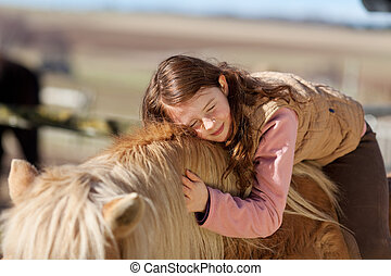 Pretty teenage girl loving her horse lying across its neck ...