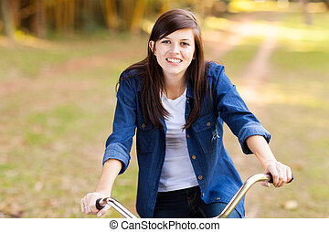 pretty teenage girl riding bike in the park