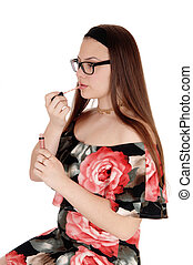 Pretty teenager girl fixing her lips in profile, wearing glasses