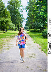 Pretty teenager girl in casual clothes going to school on...