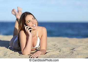 Pretty teenager girl on the phone lying on the beach