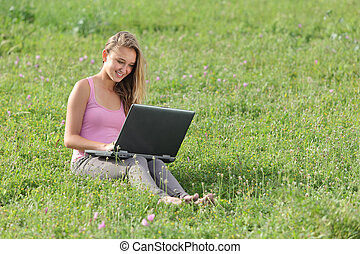 Pretty teenager girl with a laptop on the grass