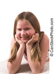 Pretty ten year old girl leaning on her hands while lying on...