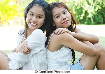 Pretty Thai girls sitting back to back