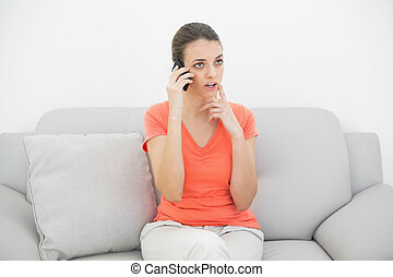 Pretty thinking woman phoning with smartphone sitting on couch