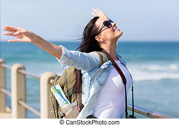 tourist standing on pier with arms outstretched - pretty...