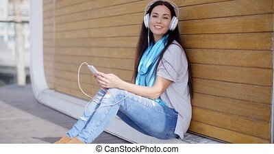 Pretty trendy young woman enjoying her music on her mobile...