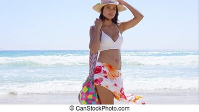 Pretty trendy young woman posing on a windy beach in a...