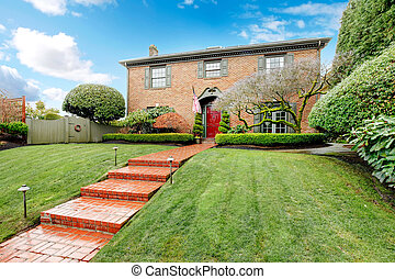 Pretty two story brick house with stoned walkway