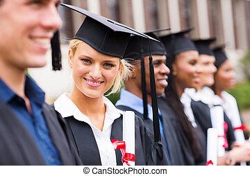 pretty university student in graduation attire looking at the camera