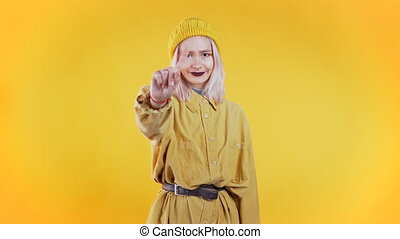 Pretty unusual girl disapproving with no crossing hands sign make negation gesture. Denying, Rejecting, Disagree, Portrait of woman on yellow background.