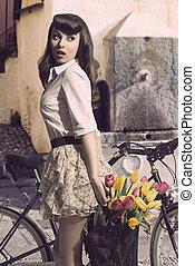 pretty vintage girl near bicycle