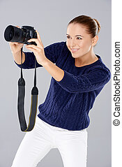 Pretty vivacious young female photographer smiling as she...