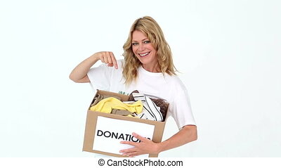 Pretty volunteer pointing to donations - Pretty volunteer...