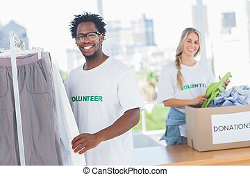 Pretty volunteers taking clothes out of a donation box