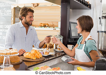 Pretty waitress serving happy customer at the coffee shop