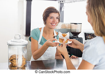 Pretty waitress serving muffin to customer at the coffee...