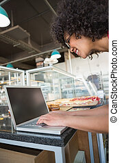 Pretty waitress smiling and using laptop