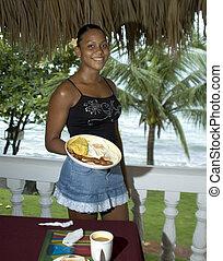 pretty waitress with breakfast on a tropical island