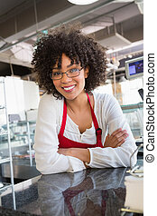 Pretty waitress with glasses leaning on counter