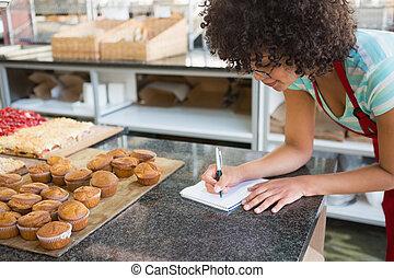 Pretty waitress writing on notebook