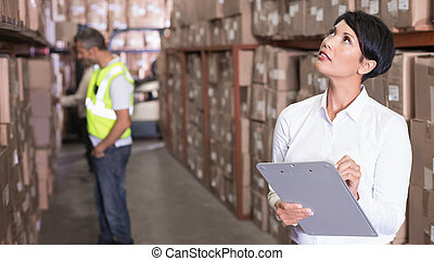 Pretty warehouse manager checking inventory in a large ...