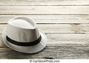 Pretty white hat on a grey wooden table