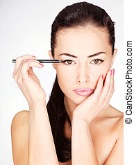 woman applying cosmetic pencil on eye - pretty woman...