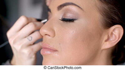 Pretty woman applying eye liner on her eyelid - Pretty dark...