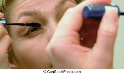 Pretty woman applying eyelashes mascara makeup