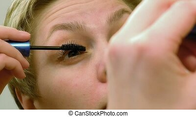 Pretty woman applying eyelashes mascara makeup