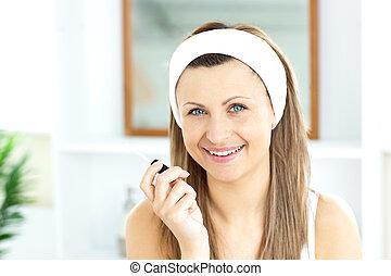 Pretty woman applying gloss on her lips in the bathroom