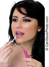 Beautiful woman applying a shade of pink lip gloss to lips