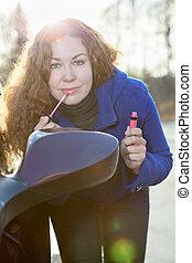 Pretty woman applying make-up near car