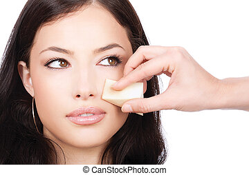 pretty woman applying make up with cosmetic sponge