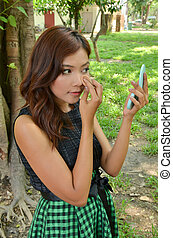 pretty woman applying make up with her cosmetic in the park