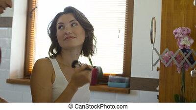 Pretty woman applying makeup on her cheek using a brush. Her smiling husband standing near