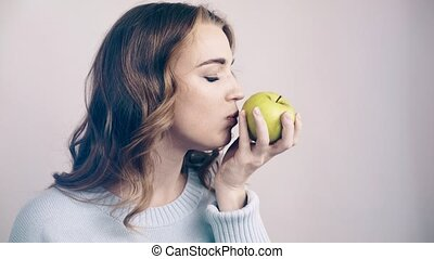 Pretty woman biting a green apple and looking at camera