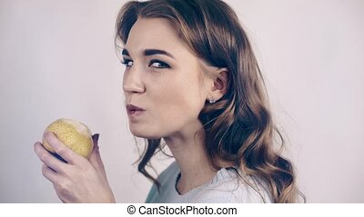 Pretty woman biting a pear and looking at camera