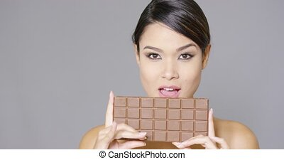 Pretty woman biting into a bar of chocolate