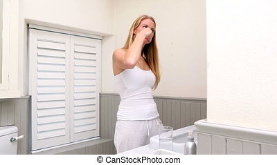 Pretty woman brushing her teeth at home in bathroom